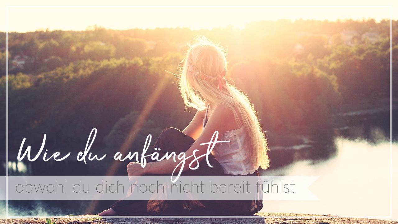 Junge Frau sitzt im Sonnenuntergang an einem See und genießt die Aussicht, Schriftzug Anfangen, obwohl du dich noch nicht bereit fühlst