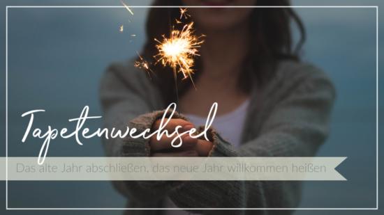 Frau hält Wunderkerze in der Dämmerung, Jahresabschluss Reflexion, Schriftzug Tapetenwechsel - das alte Jahr abschließen, das neue Jahr willkommen heißen