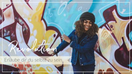 Fröhliche Frau tanzt selbstbewusst vor einer Wand mit Grafitti, Schriftzug Revolution - erlaube dir du selbst zu sein