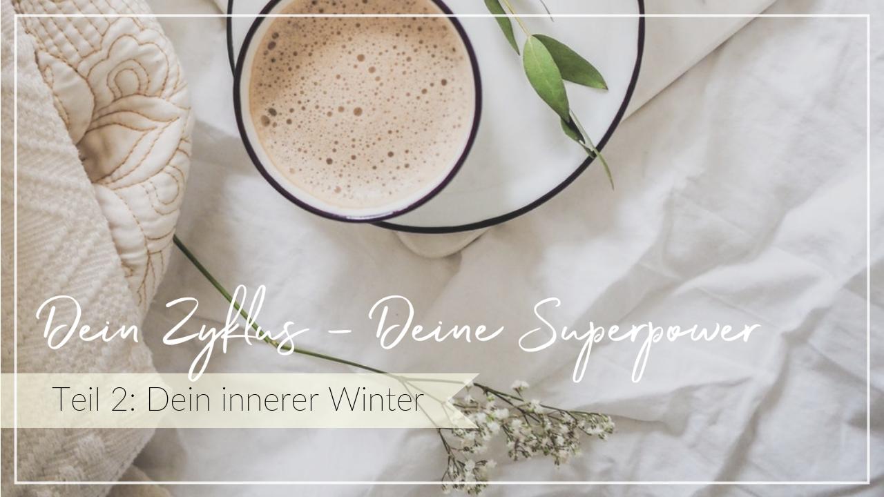 Getränk mit Milchschaum und Zweige auf einem Bett mit hellen Laken, Schriftzug Dein Zyklus, Deine Superpower, Dein innerer Winter