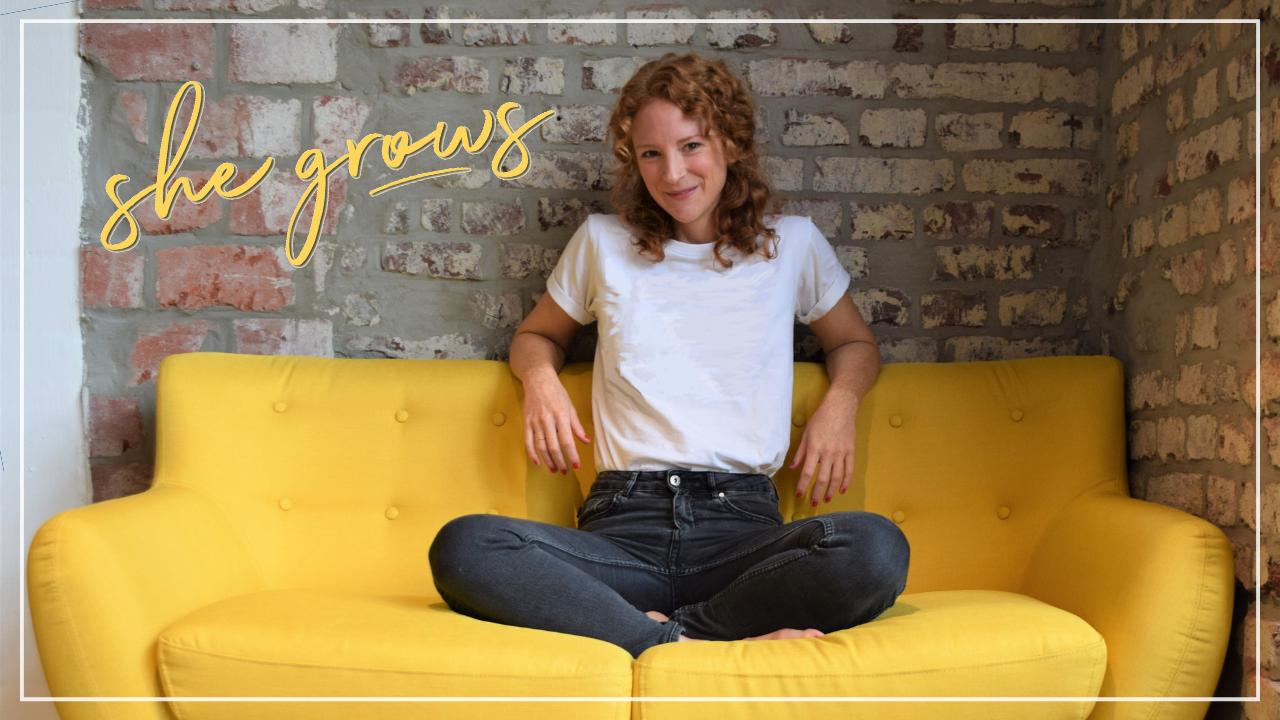 Fröhliche rothaarige Frau sitzt auf einem gelben Sofa vor einer Backsteinwand, Schriftzug she grows, Neuigkeiten rund um den Podcast, kurzes Update